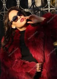 beautiful woman with dark hair wearing luxurious fur coat stock photo
