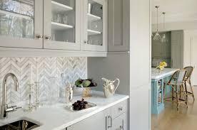 white and grey marble tile backsplash herringbone