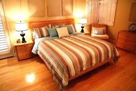 neutral bedroom design with calm color scheme also wood floors beside tables of lamp and striped