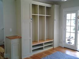 wall built in custom mudroom cubby design painted with white color with shoe rack shelves and storage with door for high entryway ceiling ideas