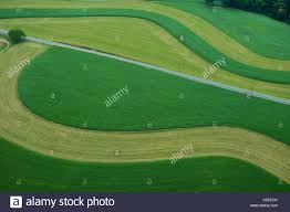 grass field aerial. Aerial View Of Agricultural Fields With Coutour Strips Young Grain Corn And Mowed Grass Cover Field