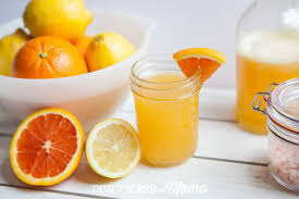a photo of an orange homemade electrolyte drink in a glass jar on a wooden surface