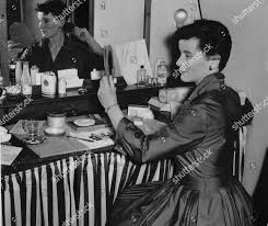 actress elizabeth bird attends to her hair and make up in the theatre dressing room