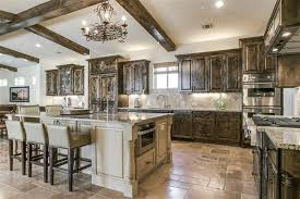 Traditional Mediterranean style kitchen with large island and exposed beam  ceiling