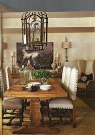 a farm table and iron details lend old world sensibilities to this neutral dining room traditional home photo eric roth design joseph abboud in