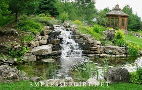 large fish pond with tall waterfall in home garden