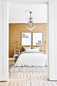 bedroom with wood planked flooring white bedding ornate chandelier wood wall with large