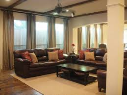 brown leather sofa with red and cream cushions also black wooden table with white rug on brown wooden floor