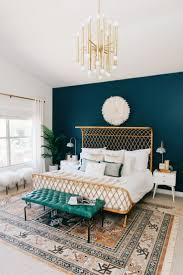 minimalist modern bedroom with white wall and navy blue wallpaper art plus pattern batik area rugs