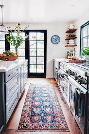 kitchen floor runners with cabinet and flower in vase on it
