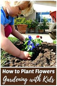 planting garden young child planting a flower in an outdoor garden bed planting gardens in graves