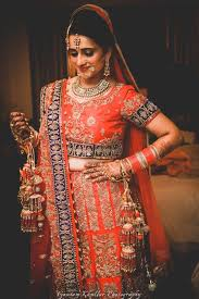 bride all ready for her wedding day in a red and blue lehenga with zari work