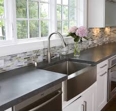 black kitchen faucets in white kitchen. silver apron sink plus faucet on white kitchen cabinet with grey countertop under the window black faucets in