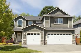 home with grey outdoor wall panel and white sectional double garage doors