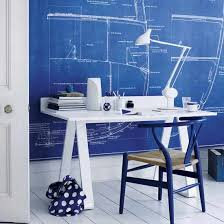 white and blue office with maritime blueprints covering walls and white washed plank floors blue office walls