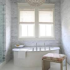 oval marble clad bathtub with white flower chandelier