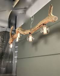 a cool pendant lamp of an old tree branch with bulbs looks really bold and chic