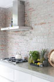 a modern white kitchen with a whitewashed red brick backsplash for a textural look