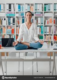 meditation office. Relaxed Woman Practicing Meditation At Home, She Is Sitting In The Lotus Position On Office Desk, Mindfulness Concept \u2014 Photo By Stokkete I