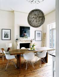dining room decor ideas modern rustic style with natural wood trestle table white eames chairs large nest light fixture and victorian fireplace