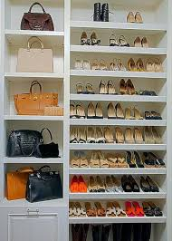 Chic walk-in closet features floor to ceiling sloped shoe shelves situated  next to a buil tin shelving unit dedicated to designer purses.