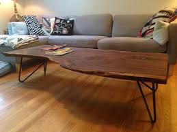 this coffee table is made from a single walnut slab the ends of the slab are reinforced with inset pieces of wood and the table sits on a set of hairpin