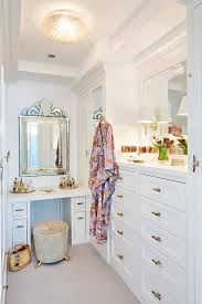 glam walk in closet features a round light gray stool on gold feet as well as a white built in makeup vanity tucked under a venetian mirror