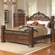 wooden bed frame with carved headboard and footboard and brown striped fabric bed sheet as well