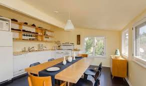pale yellow dining room. the dining room and kitchen all flow as one space with light wood exposed shelving lining pale yellow walls white cabinetry appliances
