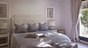 Purple And Gray Bedroom Features A Light Gray Headboard On King Bed Dressed  In Purple Pillows And Gray Blankets Flanked By White Nightstands Alongside  Gray ...