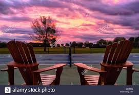 adirondack chairs overlook a tennis court during a colorful sunrise stock photo 310373296 alamy