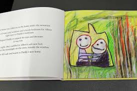 childrens book open showing a page of text and a drawing by three year
