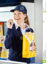 cheerful worker eating popcorn at cinema stock photo image  cheerful worker eating popcorn at cinema