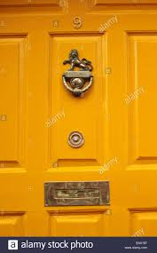 close up of a yellow door with a br knocker and letter box