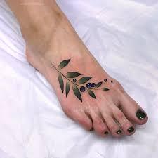 фото небольшой женской татуировки на ноге цветная веточка и ягоды по