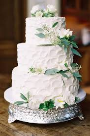 A White Textural Wedding Cake Topped With White Blooms And Greenery