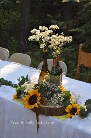 Wine bottles tied together with burlap- babies breath and sunflowers accent  the head table. Sunflower Wedding CenterpiecesWedding ...
