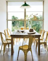 cheerful and full of light in this dinning room with rustic farm table and yellow tolix chairs