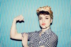 the photo is a modern interpretation of rosie the riveter she wears a plaid blue