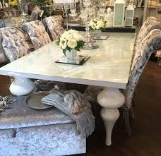 white gloss dining table high with multi coloured chairs