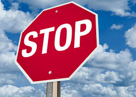Image: bright red stop sign against a blue sky with white puffy clouds