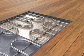 radiant heat flooring pipes exposed in a newly installed wood floor