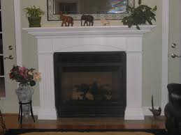 interior white wooden mantel shelf over black iron fire box on grey wall and