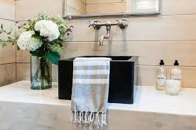 cottage style bathroom fitted with a marble floating vanity countertop a black vessel sink and gray shiplap walls