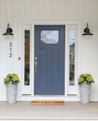 glossy black vintage barn sconces are mounted to a white paneled home exterior on either side of a blue front door accented with a single glass panel