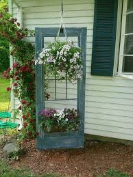 an old door is used in the garden as a plant holder display