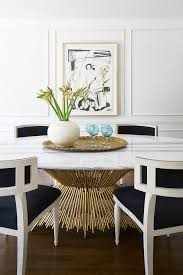 gorgeous dining room boasts an oval br and marble dining table lined with white and black french dining chairs placed before a wall accented with