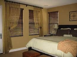 light brown master bedroom with three section window using dark brown venetian blinds and gold brown