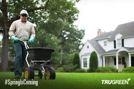 p trugreen lawn specialist using a seed spreading machine on a lawn