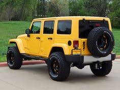 2018 jeep wrangler unlimited sahara in baja yellow equipped with a lift kit and custom tires and wheels jeepwrangler